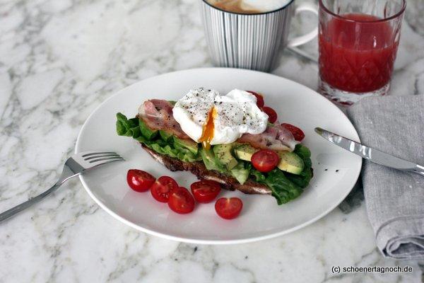 Sonntagsfrühstück: Pochiertes Ei auf geröstetem Brot mit Salat, Avocado, Bacon und Kirschtomaten