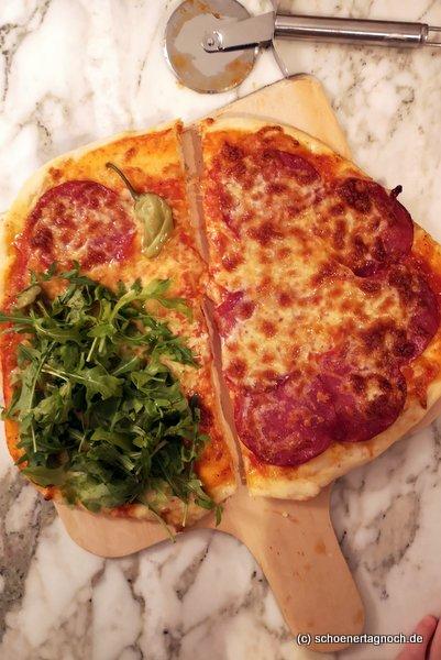 Selbstgemachte Pizza mit Salami und Rucola