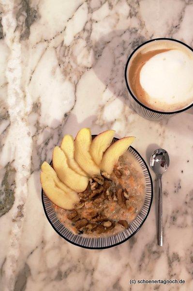 Warmes Carrot Cake Porridge mit Apfelscheiben und Walnüssen.