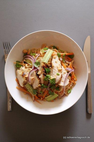 Thai-Reisnudelsalat mit Karotten, Gurken, Frühlingszwiebeln, gebratener Hähnchenbrust, gerösteten Erdnüssen und Koriander
