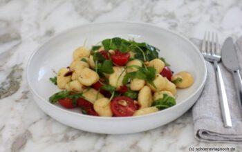 Lauwarmer Gnocchi-Salat mit Rucola, Kirschtomaten und gerösteten Pinienkernen