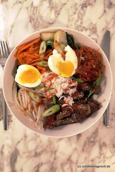 Selbst gekochtes Bibimbap mit Rindfleisch, Reis, Kimchi, Mungobohnensprossen, Karotten, Pak Choi, Spinat und wachsweichem Ei